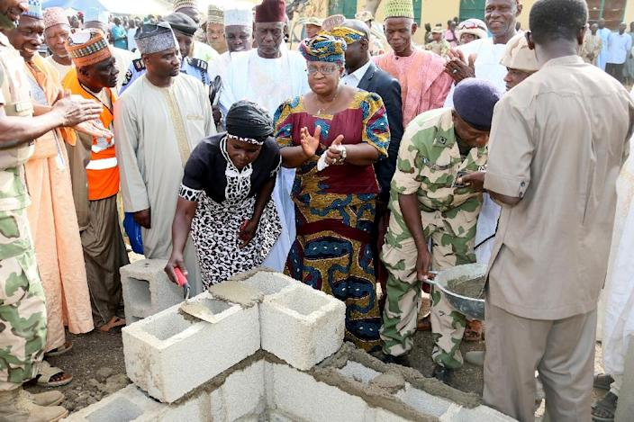 The mother of a missing Chibok schoolgirl lays the foundation for new classrooms at a school burned out by Boko Haram Islamist fighters in Chibok, Nigeria, March 5, 2015 (AFP Photo/Sunday Aghaeze)