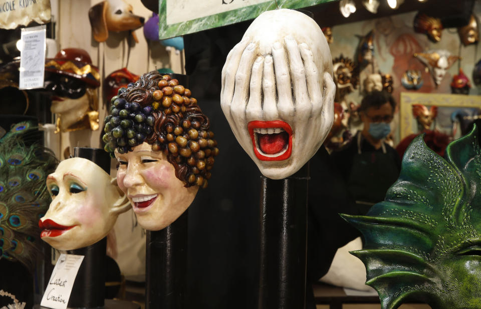 Carnival masks on display in a shop window in Venice, Italy, Saturday, Jan. 30, 2021. In another year, masks would be an accepted sign of gaiety in Venice, an accessory worn for games, parties and crowds. Since the onset of the COVID-19 pandemic face masks are worn now to protect, not amuse. (AP Photo/Antonio Calanni)