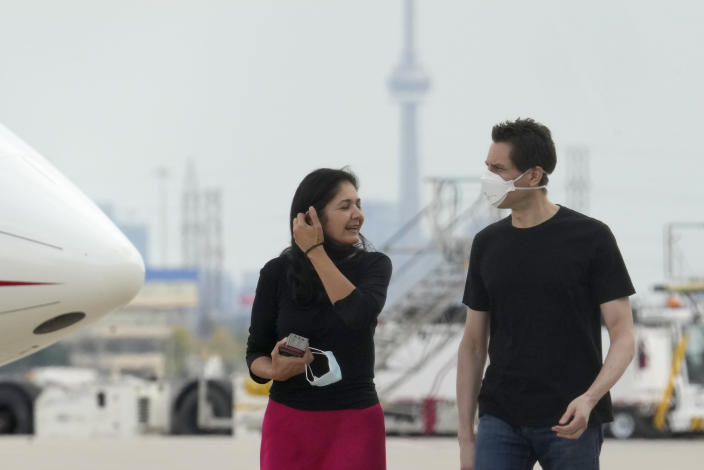 Michael Kovrig, right, talks with his wife Vina Nadjibulla, center left, after his arrival at Pearson International Airport in Toronto, Saturday, Sept. 25, 2021. China, the U.S. and Canada completed a high-stakes prisoner swap Saturday with joyous homecomings for Kovrig and Michael Spavor, two Canadians held by China and for an executive of Chinese global communications giant Huawei Technologies charged with fraud. (Frank Gunn /The Canadian Press via AP)