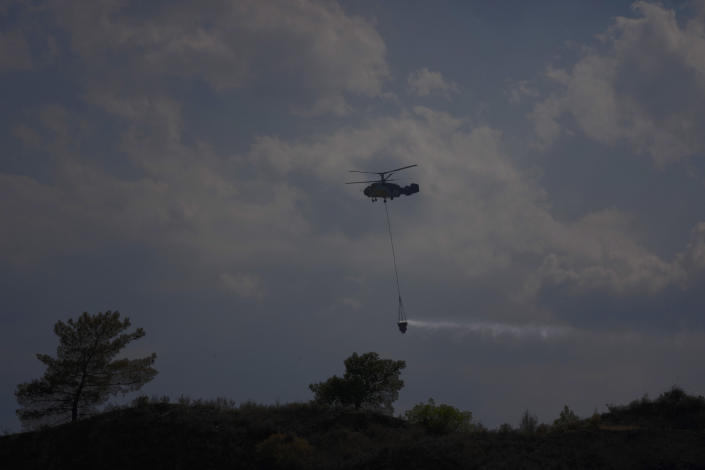 """A helicopter flies over the burned Larnaca mountain region near Ora village, Cyprus, Sunday, July 4, 2021. Cyprus' interior minister says four people have died in what he called the """"most destructive"""" fire in the island nation's history. (AP Photo/Petros Karadjias)"""