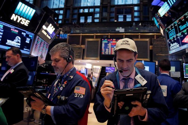 Traders work on the floor at the New York Stock Exchange (NYSE) in Manhattan, New York City, U.S., December 21, 2016. REUTERS/Andrew Kelly/Files