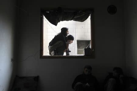 Abu Nejme, a 21-year-old Free Syrian Army fighter, is carried by a fellow fighter in Aleppo
