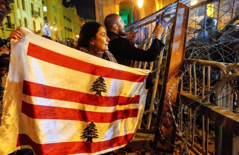 FILE PHOTO: A demonstrator holds the Lebanese flag during a protest against a ruling elite accused of steering Lebanon towards economic crisis in Beirut