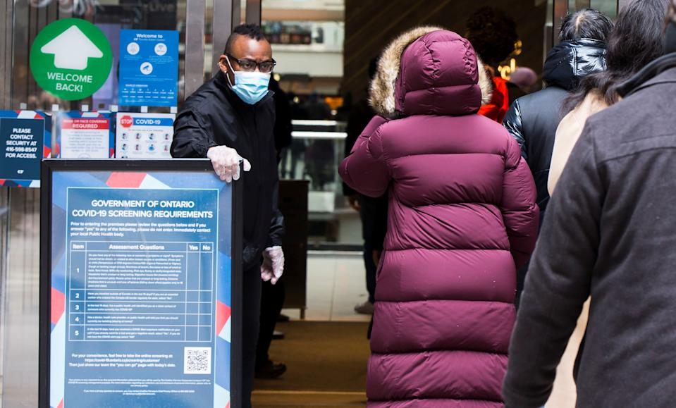 TORONTO, March 8, 2021 -- A security officer wearing a face mask checks customers' health screening results at the entrance of CF Toronto Eaton Center in Toronto, Canada, on March 8, 2021. A stay-at-home order in Toronto, Peel Region, and North Bay was lifted Monday as the province loosens pandemic restrictions. The three regions were the last ones still under the order, and are transitioning back to the government's color-coded pandemic response framework. (Photo by Zou Zheng/Xinhua via Getty) (Xinhua/Zou Zheng via Getty Images)