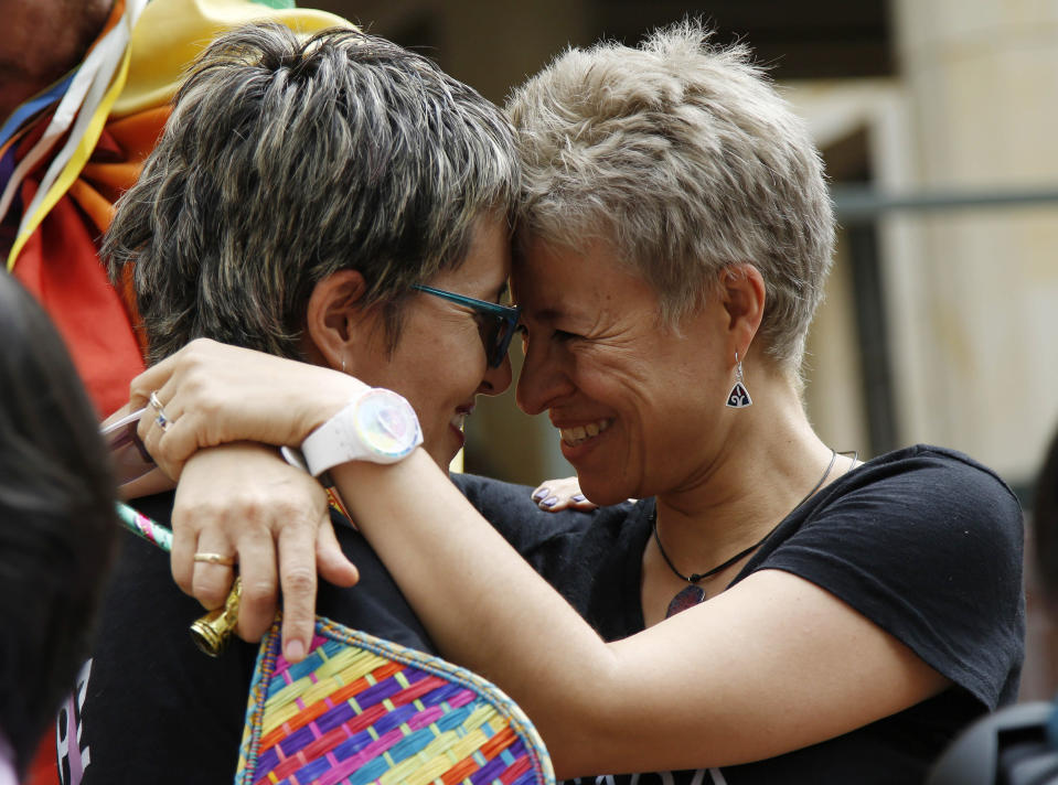 LGBT rights activists Sandra Rojas, left, and Adriana Gonzalez celebrate a Constitutional Court decision to give same-sex couples marriage rights, in front of the Justice Palace in Bogota, Colombia, Thursday, April 7, 2016. (AP Photo/Fernando Vergara)