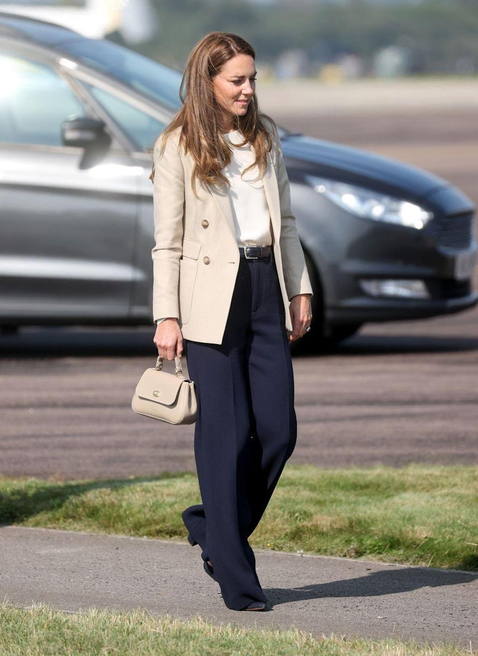 """<p>The Duchess of Cambridge returned to royal duties after her summer break and she did so sporting the perfect back-to-work outfit. While <a href=""""https://www.townandcountrymag.com/society/tradition/a37596711/kate-middleton-cream-blazer-navy-trousers-raf-visit-photos/"""" rel=""""nofollow noopener"""" target=""""_blank"""" data-ylk=""""slk:visiting a Royal Air Force military base"""" class=""""link rapid-noclick-resp"""">visiting a Royal Air Force military base</a>, she wore a <a href=""""https://go.redirectingat.com?id=74968X1596630&url=https%3A%2F%2Fwww.reiss.com%2Fp%2Fdouble-breasted-twill-blazer-womens-larsson-in-neutral-brown%2F&sref=https%3A%2F%2Fwww.townandcountrymag.com%2Fstyle%2Ffashion-trends%2Fnews%2Fg1633%2Fkate-middleton-fashion%2F"""" rel=""""nofollow noopener"""" target=""""_blank"""" data-ylk=""""slk:neutral Reiss blazer"""" class=""""link rapid-noclick-resp"""">neutral Reiss blazer</a> and wide leg navy trousers. </p>"""