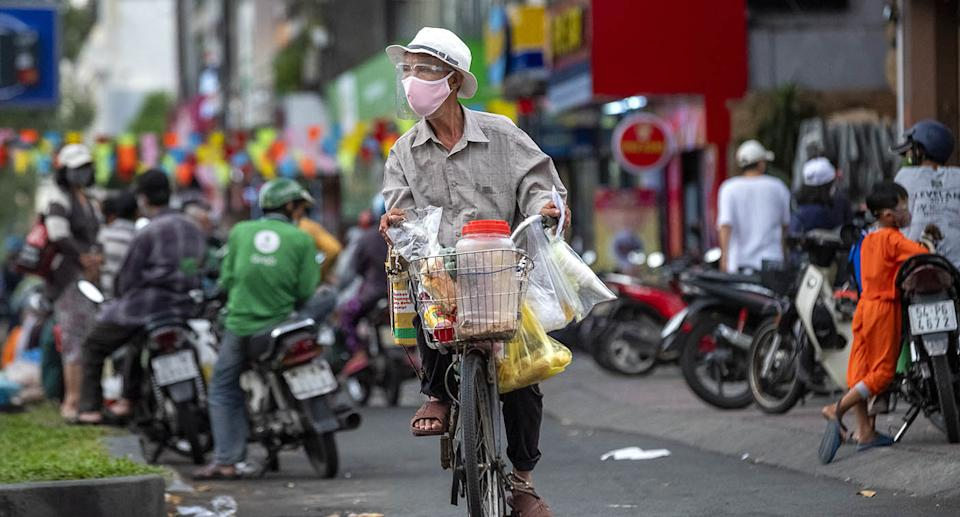 A man rides a bicycle with a mask on during a surge of Covid infections in Vietnam.