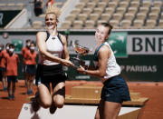 Czech Republic's Barbora Krejcikova, right, and compatriot Katerina Siniakova jump while holding the cup after defeating USA's Bethanie Mattek-Sands and Poland's Iga Swiatek in their women's doubles final match of the French Open tennis tournament at the Roland Garros stadium Sunday, June 13, 2021 in Paris. Czech Republic's Barbora Krejcikova playing with fellow Cezch player Katerina Siniakova, won the doubles final 6-4, 6-2. (AP Photo/Thibault Camus)