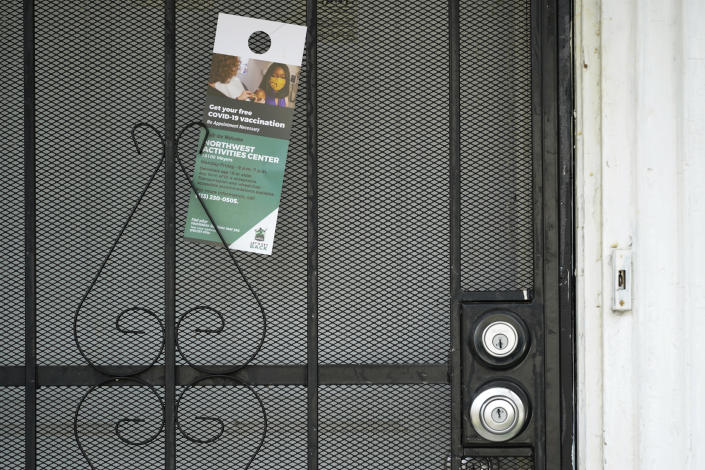 A flyer is shown left on a home in Detroit, Tuesday, May 4, 2021. Officials are walking door-to-door to encourage residents of the majority Black city to get vaccinated against COVID-19 as the city's immunization rate lags well behind the rest of Michigan and the United States. (AP Photo/Paul Sancya)