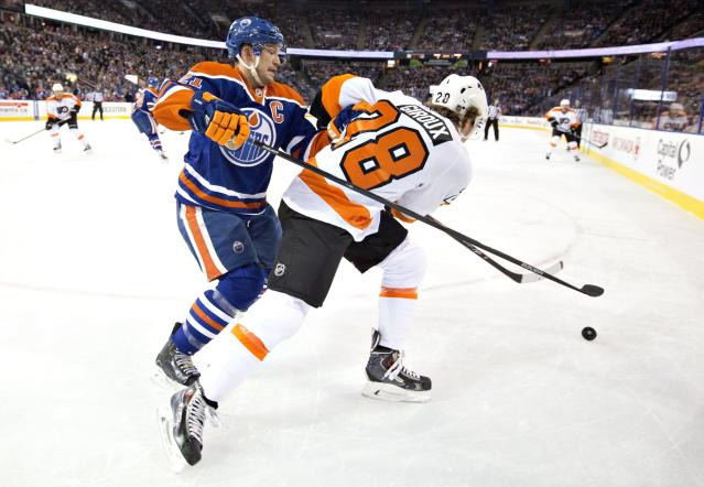 Philadelphia Flyers' Claude Giroux (28) battles with Edmonton Oilers' Andrew Ference (21) during the first period of an NHL hockey game on Saturday, Dec. 28, 2013, in Edmonton, Alberta. (AP Photo/The Canadian Press, Jason Franson)