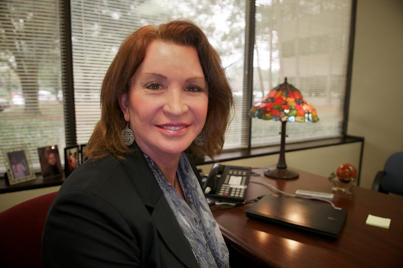 In this Feb. 11, 2011 photo, Gina Duncan, a transgender employee, sits at her Wells Fargo office in Maitland, Fla.  More and more large corporations, including Coca-Cola, Campbell Soup and Walt Disney, are covering surgery for transgender employees as part of their health plans. The trend follows a concerted push by transgender rights advocates to get employers and insurers to see sex reassignment the way the American Medical Association does — as a medically indicated rather than an optional procedure.   (AP Photo/Roberto Gonzalez)