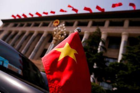 FILE PHOTO: The Vietnamese national flag flies on a diplomatic car outside the Great Hall of the People before talks between Vietnam's President Tran Dai Quang and Chinese leaders in Beijing
