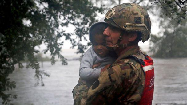 PHOTO: Rescue team member Sgt. Nick Muhar, from the North Carolina National Guard 1/120th battalion, evacuates a young child as the rising floodwaters from Hurricane Florence threatens his home in New Bern, N.C., on Friday, Sept. 14, 2018. (AP)