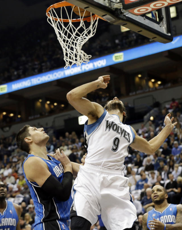Minnesota Timberwolves' Ricky Rubio, right, of Spain, and Orlando Magic's Nikola Vucevic, of Montenegro, watch Rubio's shot fall in the basket in the first quarter of an NBA basketball game, Wednesday, Oct. 30, 2013 in Minneapolis. (AP Photo/Jim Mone)