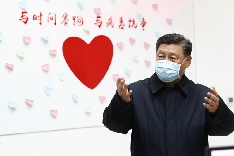 """Xi Jinping gestures near a heart shape sign and the slogan """"Race against time, Fight the Virus"""". Source: AP"""