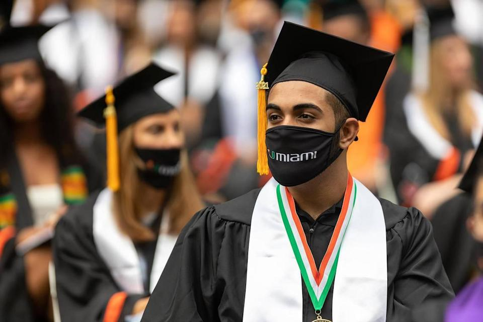 Two students sit at one of the commencement ceremonies of the University of Miami held at the Hard Rock Stadium in Miami Gardens on Friday, May 14, 2021.