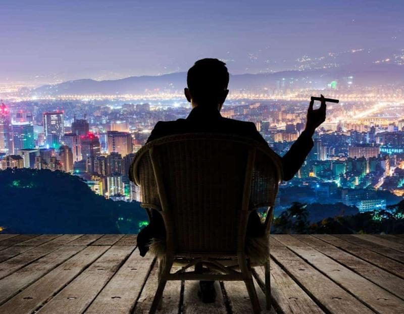 Silhouette of businessman sit on chair and hold a cigar and looking at the city in night.