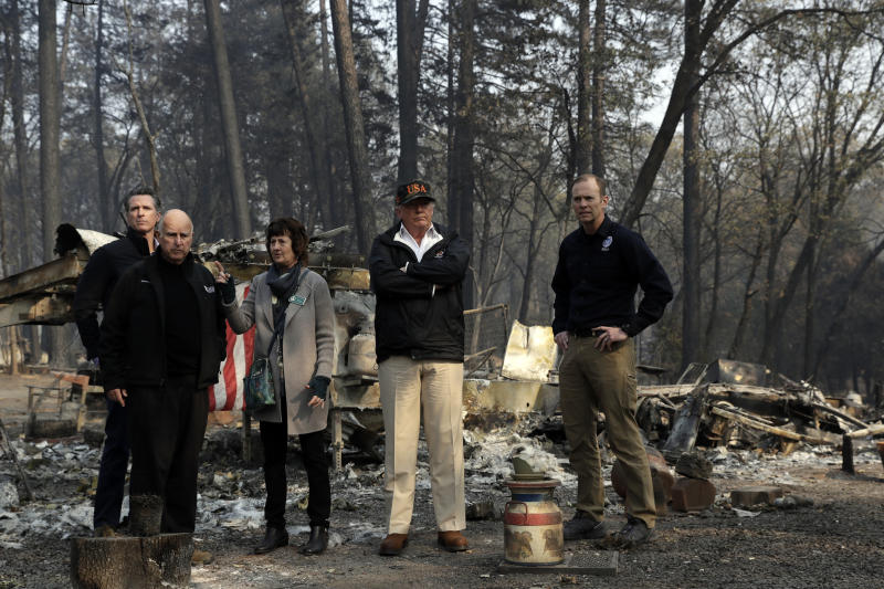 FILE - In this Nov. 17, 2018 file photo, President Donald Trump talks with from left, Gov.-elect Gavin Newsom, California Gov. Jerry Brown, Paradise Mayor Jody Jones and FEMA Administrator Brock Long during a visit to a neighborhood destroyed by the wildfires in Paradise, Calif. President Donald Trump is threatening to withhold Federal Emergency Management Agency money to help California cope with wildfires if the state doesn't improve its forest management practices. Trump tweeted Wednesday, Jan. 9, 2019, that California gets billions of dollars for fires that could have been prevented with better management. (AP Photo/Evan Vucci, File)