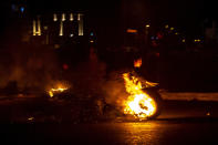 Protesters burn tires to close a main road, at Martyrs Square, in downtown Beirut, Lebanon, Saturday, March 6, 2021. Lebanon's caretaker prime minister warned Saturday that the country was quickly headed toward chaos and appealed to politicians to put aside differences in order form a new government that can attract desperately needed foreign assistance. (AP Photo/Hassan Ammar)