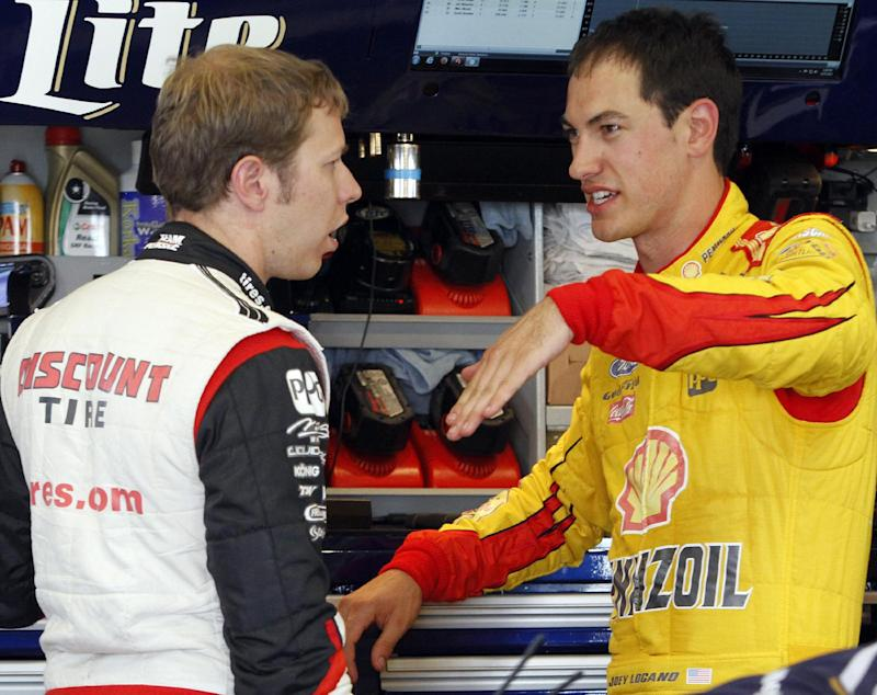 Drivers Brad Keselowski, left, and Joey Logano compare notes in the garage during practice for the NASCAR Sprint Cup series auto race at the Kentucky Speedway in Sparta, Ky., Friday, June 27, 2014