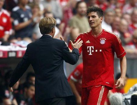 File Photo - Mario Gomez of FC Bayern Munich receives congratulations by interim coach Andries Jonker during their German first division Bundesliga soccer match against VfB Stuttgart in Munich May 14, 2011.  REUTERS/Michael Dalder