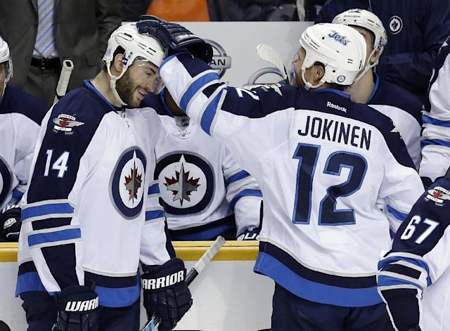 Winnipeg Jets right wing Anthony Peluso (14) celebrates with Olli Jokinen (12), of Finland, after Peluso scored against the Nashville Predators in the second period of an NHL hockey game on Thursday, Oct. 24, 2013, in Nashville, Tenn. (AP Photo/Mark Humphrey)