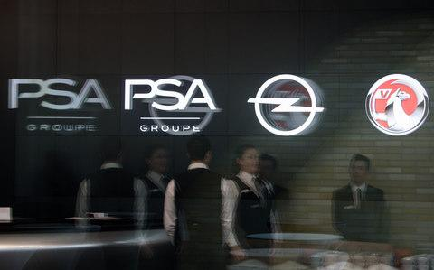 PSA, Opel and Vauxhall logos on display at the conference where the new strategy was revealed - Credit: Bloomberg
