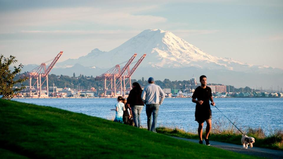 Seattle, USA - October 5, 2013: A family and a man jogging with his dog just before sunset in Myrtle Edwards Park with a view of Mount Rainier.