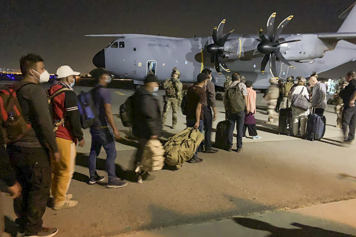 People line up to board a French military transport plane