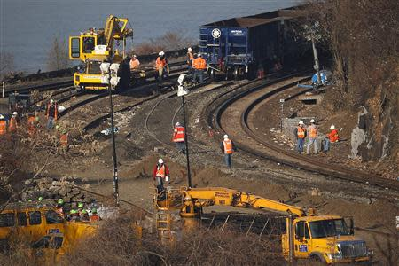 Workers are seen on the tracks of the Metro-North train derailment in the Bronx borough of New York