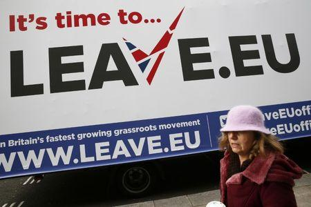 A woman walks past a Leave.EU campaign mobile advertising board in central London