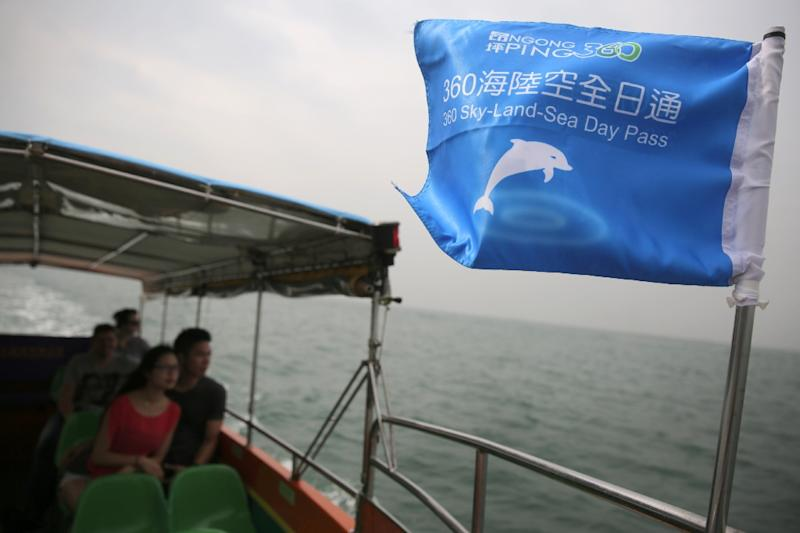 Customers on a boat tour to see the famous pink dolphins around the waters of Tai O in Hong Kong (AFP Photo/Isaac Lawrence)