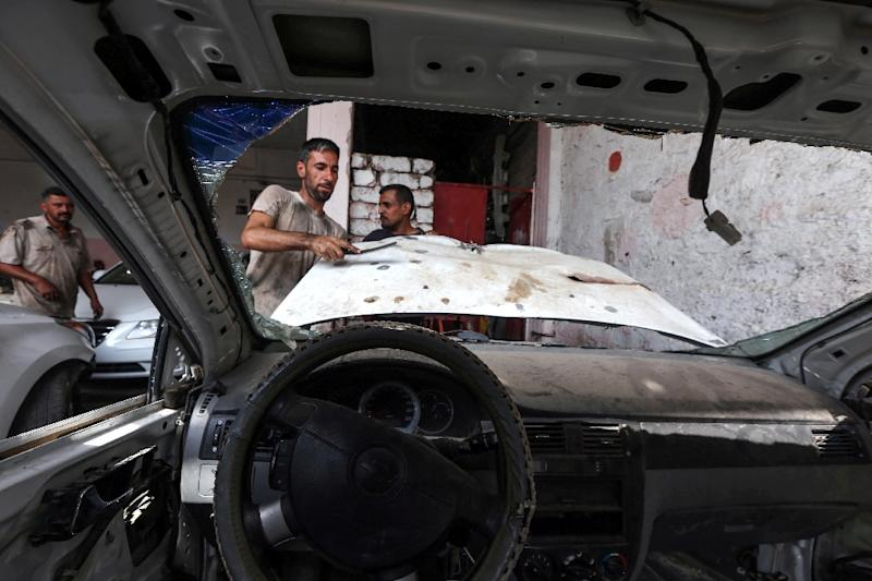 An Iraqi mechanic works on a car damaged by fighting in Mosul on September 6, 2017 (AFP Photo/SAFIN HAMED)