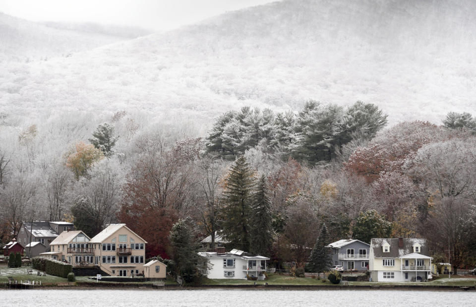 Snow clings to the hills behind a row of lake houses on Pontoosuc Lake in Pittsfield, Mass., Friday, Oct. 30, 2020. The first snowfall of the season hit New England with a light dusting. (Ben Garver/The Berkshire Eagle via AP)