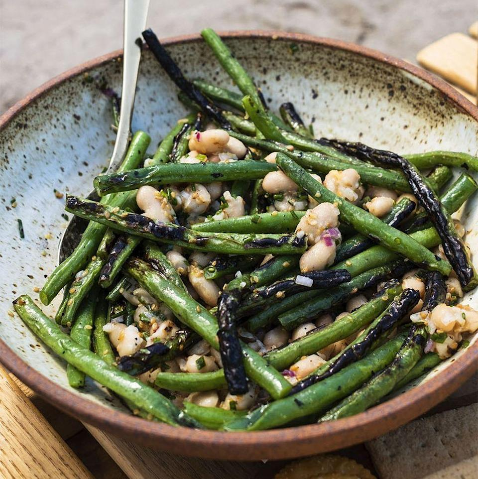"""<p>You can never have too many green beans. In this recipe, crunchy green beans are mixed with white beans to make a hearty and healthy salad.</p><p><strong><em><a href=""""https://www.womansday.com/food-recipes/a36902905/grilled-green-bean-salad-recipe/"""" rel=""""nofollow noopener"""" target=""""_blank"""" data-ylk=""""slk:Get the Grilled Green Bean Salad recipe."""" class=""""link rapid-noclick-resp"""">Get the Grilled Green Bean Salad recipe.</a></em></strong></p>"""