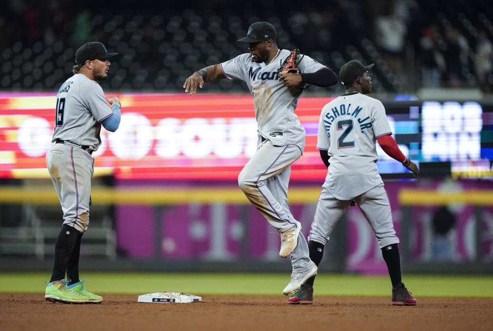Miami Marlins' Miguel Rojas, Starling Marte and Jazz Chisholm Jr., from left, celebrate the team's 6-5 win against the Atlanta Braves in 10 innings in a baseball game Wednesday, April 14, 2021, in Atlanta. (AP Photo/Brynn Anderson)