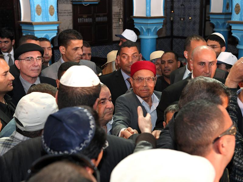 President Moncef Marzouki, center, shakes hands as he visits the synagogue on Djerba island, Tunisia Wednesday, April 11, 2012, marking the 10th anniversary of an al-Qaida truck bomb at the synagogue that killed 21 people. It comes at a time when Tunisia's small, 1,500-strong, Jewish community is facing pressure from ultraconservative Muslim groups, after an uprising last year overthrew Tunisia's decades-old secular dictatorship. (AP Photo/Str)
