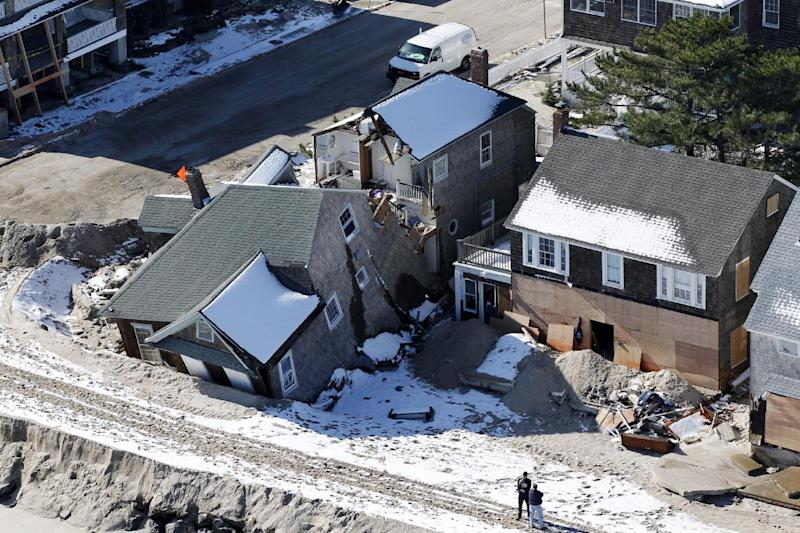 FILE - In this Nov. 9, 2012 aerial-file photo, people stand near damaged homes along the Atlantic Ocean in New Jersey after the region was pounded by Superstorm Sandy. Man-made global warming may decrease the likelihood of the already unusual steering currents that pushed Superstorm Sandy due west into New Jersey in a freak 1-in-700 year path, researchers report. While that may sound like the rare good climate change news, it's probably not, according to the study's authors, because they only looked at steering currents and other factors, including stronger storms, and sea level rise can and likely will outweigh any benefit from changing air patterns. The study is disputed by other scientists who have been vocal about the meteorological factors behind Sandy. (AP Photo/Mel Evans, File)