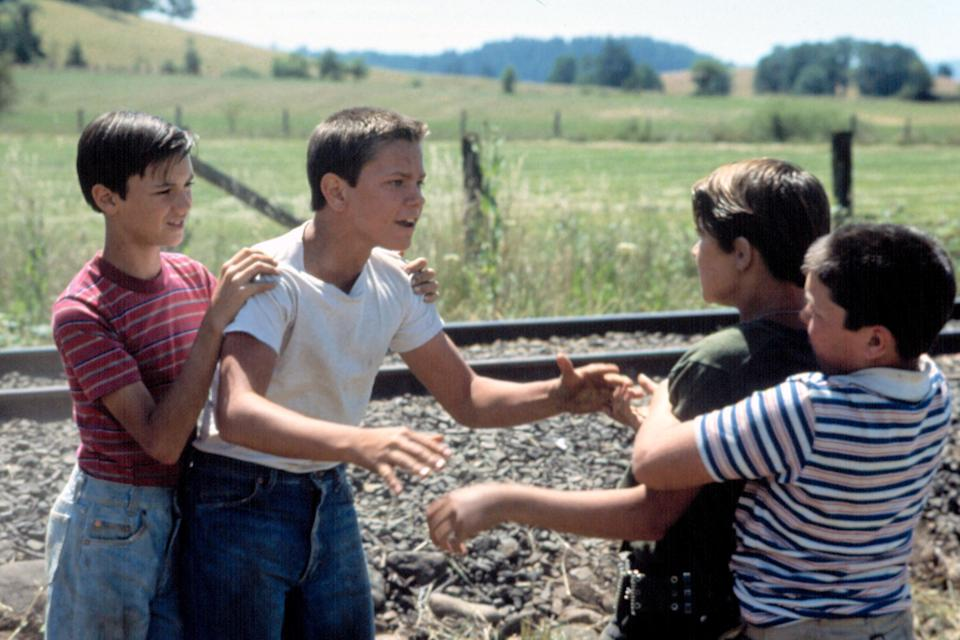 Four boys in pairs of two looking like they're about to fight next to some train tracks, field, and hills with trees in the background