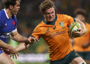 Australia's Michael Hooper runs in to score a try as France's Damian Penaud, left, attempts a tackle during the second rugby test between France and Australia in Melbourne, Australia, Tuesday, July 13, 2021. (AP Photo/Asanka Brendon Ratnayake)