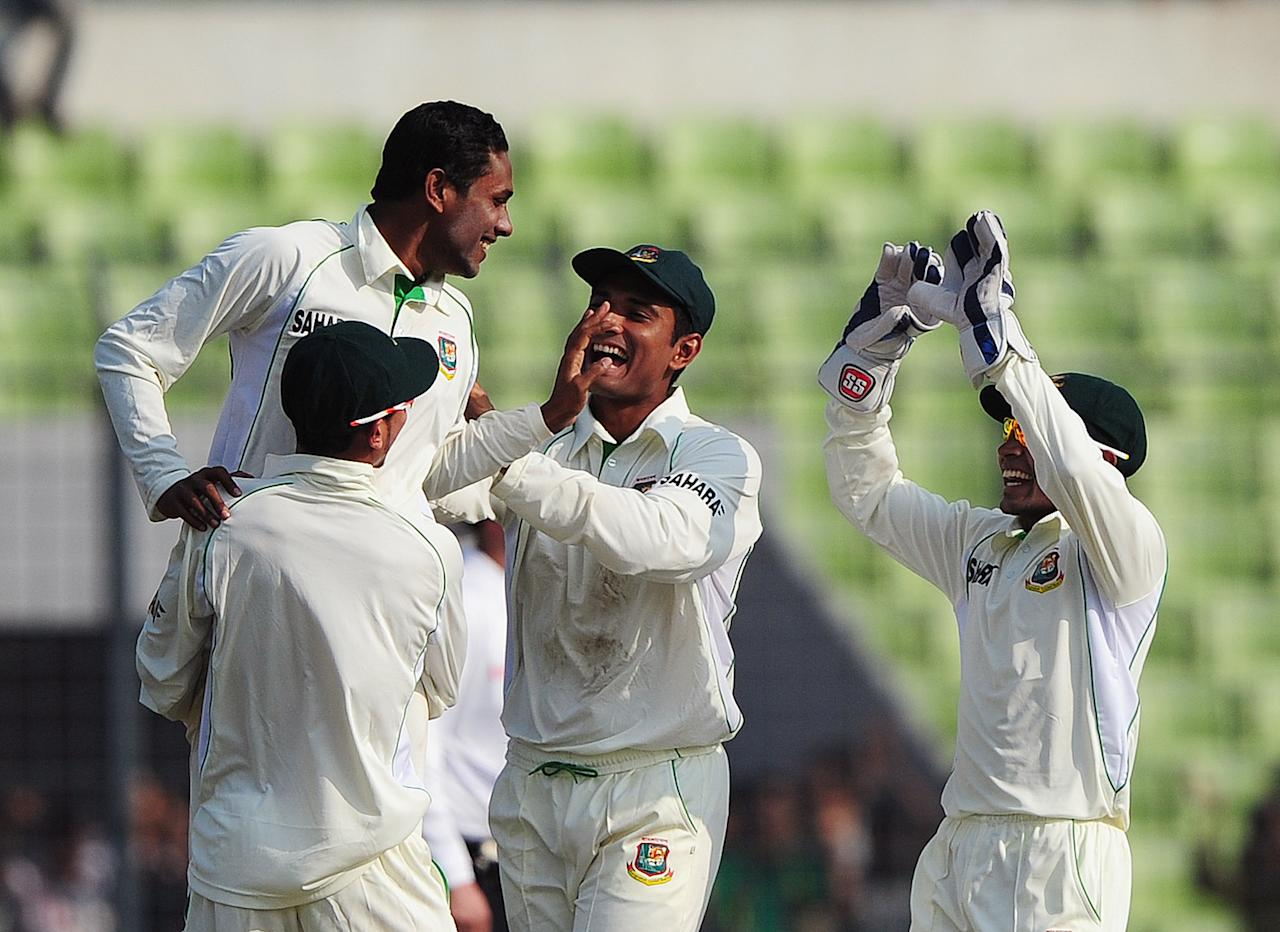 Bangladesh cricketer Sohag Gazi (L) celebrates with teammates the dismissal of West Indies cricketer Kieran Powell during the first day of the first Test match between Bangladesh and West Indies at the Sher-e-Bangla National Cricket Stadium in Dhaka on November 13, 2012.  AFP PHOTO/ Munir uz ZAMAN