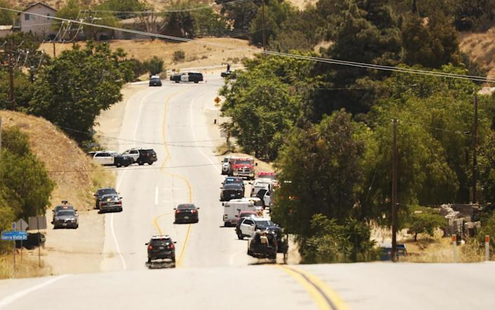 Emergency vehicles line a hilly road.