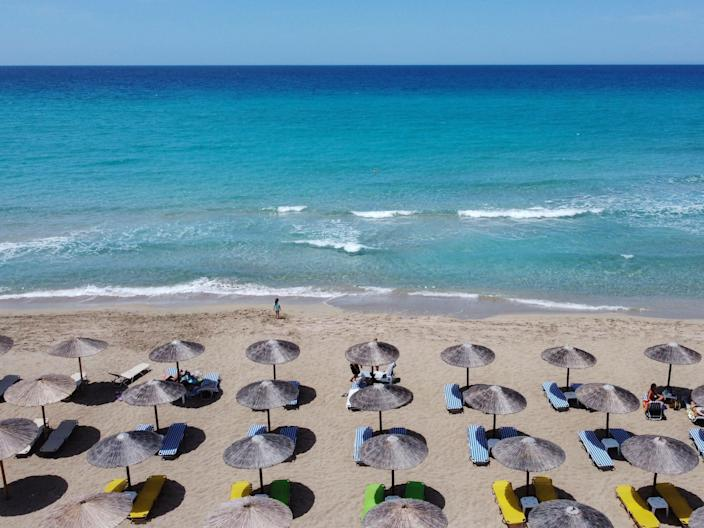 An overhead photo of blue water, sand, and umbrellas on a beach in Greece.