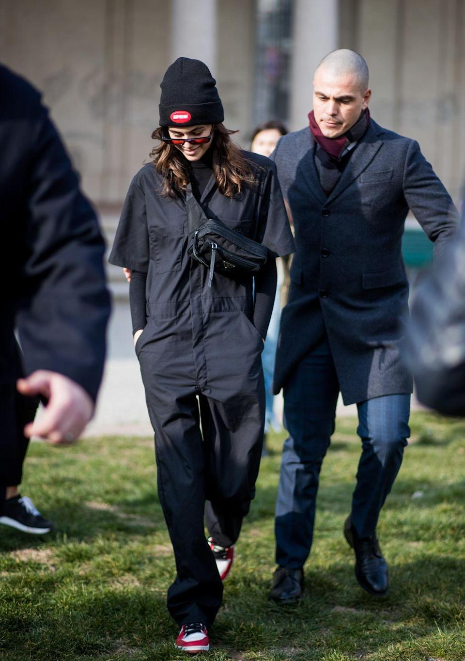 <p>The Californian beauty wore a black boiler suit inspired jumpsuit with cat-eye sunglasses and a back hat</p>