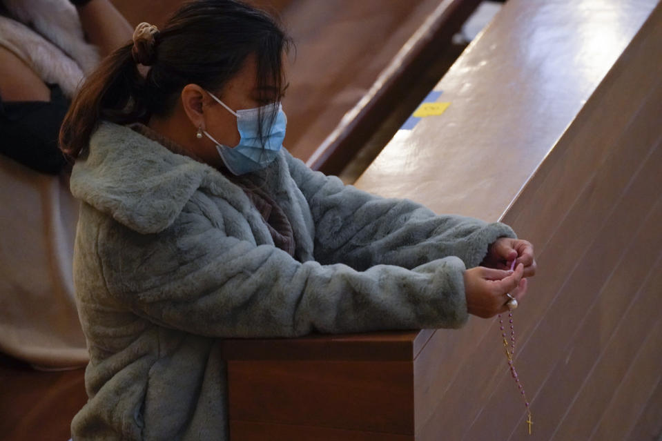 A woman wearing a mask holds a rosary during a Christmas Eve Mass inside the Cathedral of Our Lady of the Angels, Thursday, Dec 24, 2020, in Los Angeles. California became the first state to record 2 million confirmed coronavirus cases, reaching the milestone on Christmas Eve as nearly the entire state was under a strict stay-at-home order and hospitals were flooded with the largest crush of cases since the pandemic began. (AP Photo/Ashley Landis)