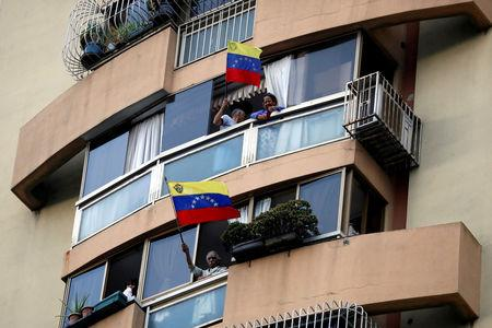 People wave the national flag from their windows during a protest against President Nicolas Maduro's government in Caracas, Venezuela, March 12, 2019. REUTERS/Carlos Garcia Rawlins