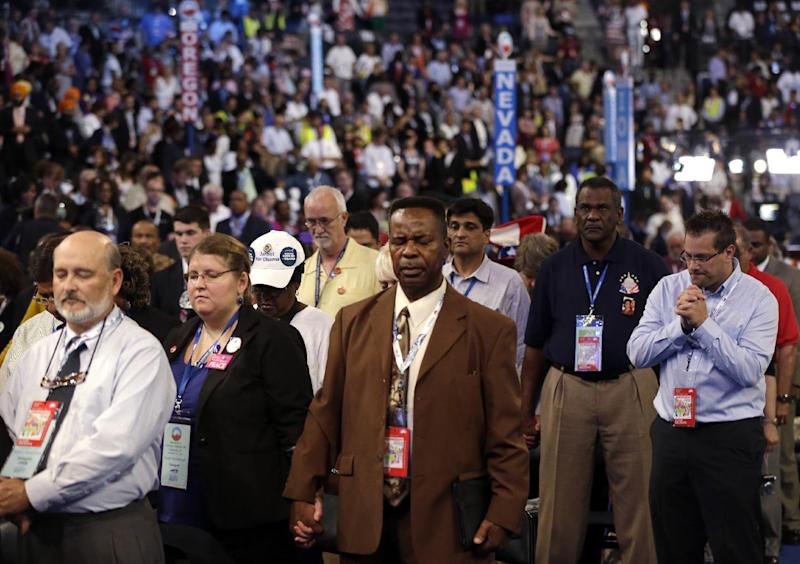 """In this Sept. 5, 2012, photo, delegates pray during the Democratic National Convention in Charlotte, N.C. The placards on display as former President Bill Clinton addressed the DNC said, """"Middle Class First."""" The rich also have featured in the rhetoric, albeit as a punching bag. But the poor? Not so much. They've been mentioned only fleetingly. The discrepancy makes sense, from the standpoint of campaign strategy for President Barack Obama. A large majority of Americas identify themselves as middle class, while the poor lack political clout for a host of reasons. Yet for a party that has long embraced a role as defender of the downtrodden, the rhetorical patterns are striking.(AP Photo/Charles Dharapak)"""