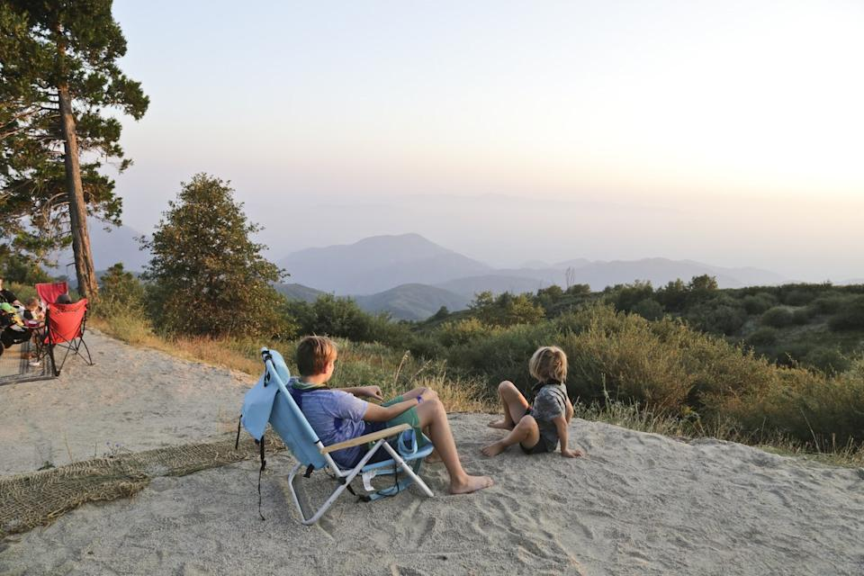 Two kids at a campsite looking at the view of the mountains.