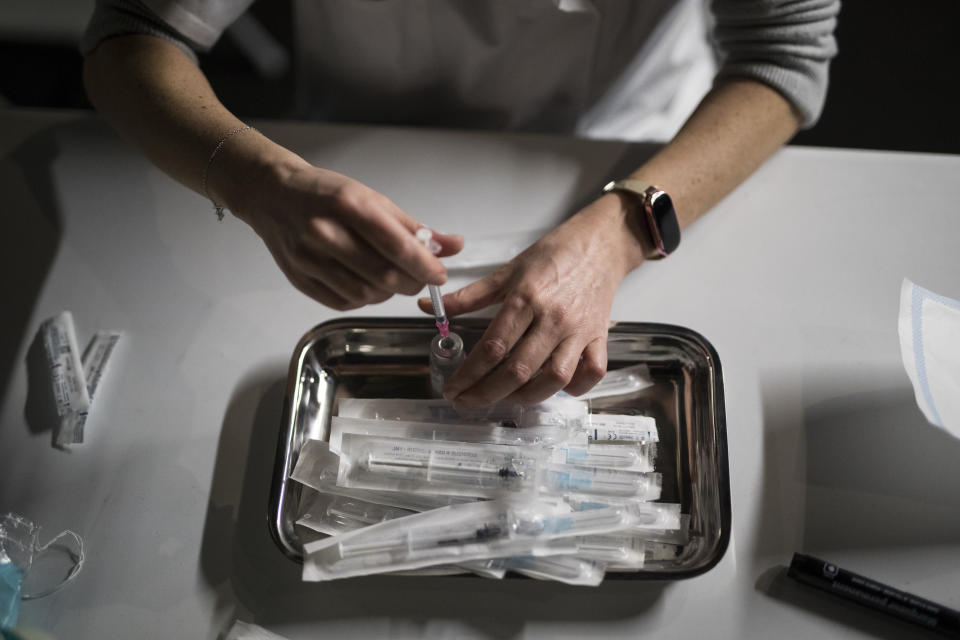 Nurse Coralie Ferron prepares doses of the Moderna COVID-19 vaccine at a vaccination center in Le Cannet, southern France, Thursday Jan. 21, 2021. (AP Photo/Daniel Cole)