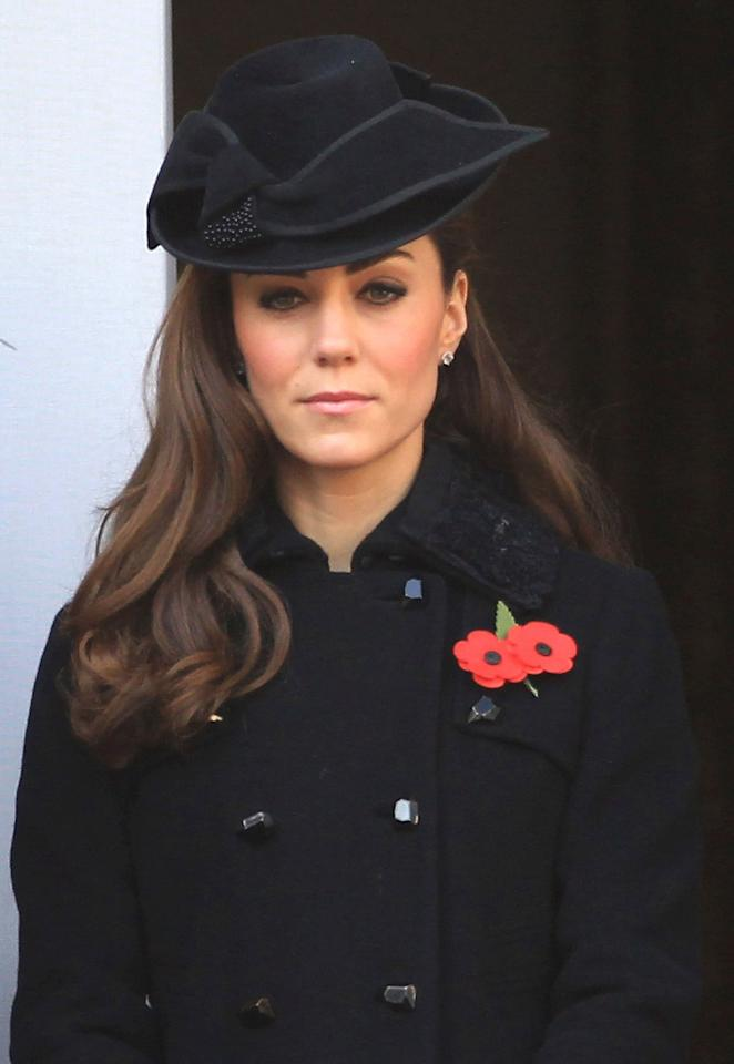 """Making her Remembrance Day debut, Kate, who wore her hair down, opted for a simple black hat with a bow to one side for the <a href=""""https://people.com/royals/see-meghan-harry-kate-and-william-join-the-queen-for-solemn-remembrance-day-ceremony/"""">solemn ceremony</a>, during which the royal family honors those who lost their lives in war.  She would go on to re-wear the fashionable headpiece in 2014. She also had on the same jacket she wore in 2012 and 2016."""